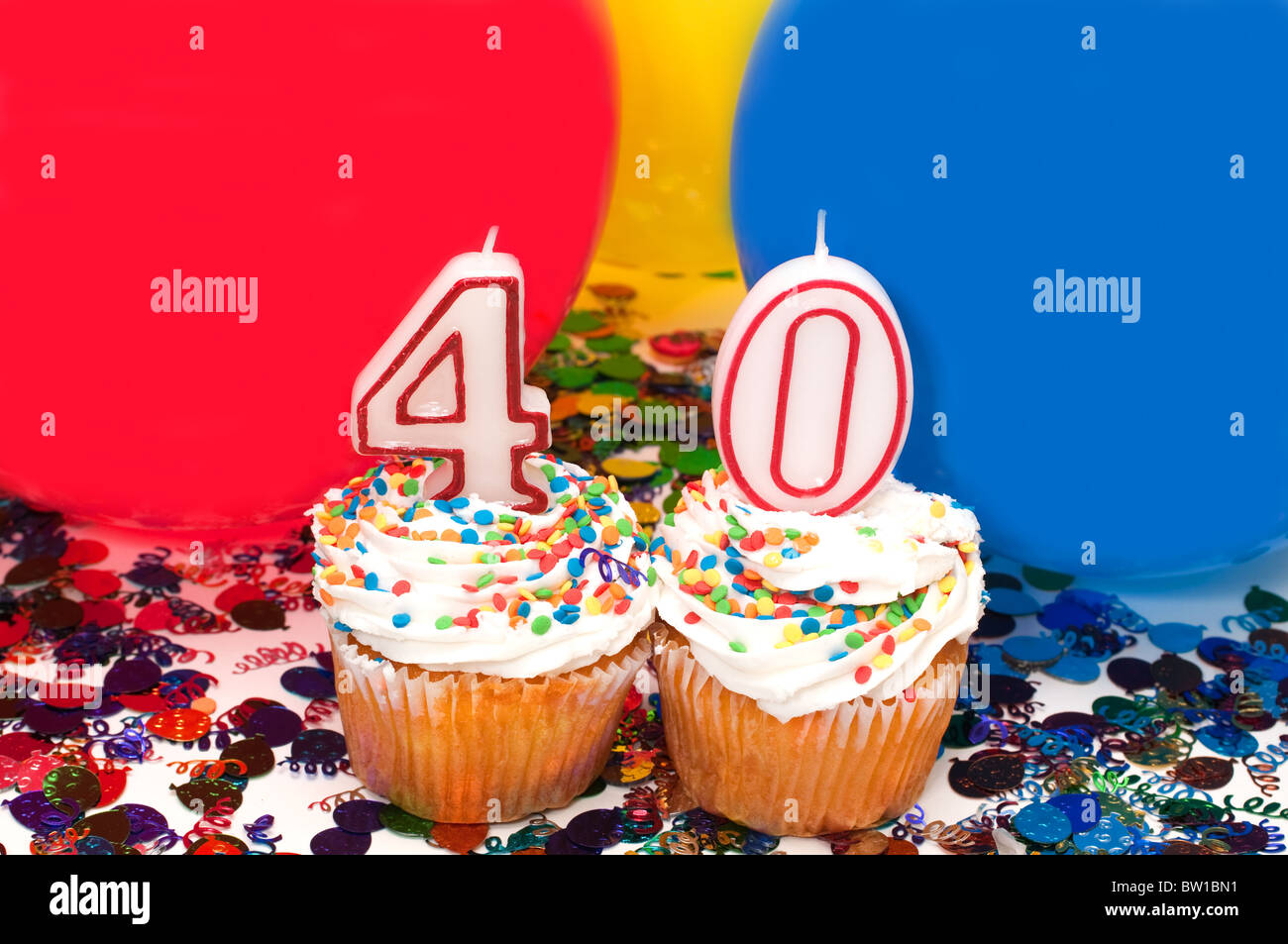 Celebration with balloons, confetti, cupcake, and number 40 candle. - Stock Image