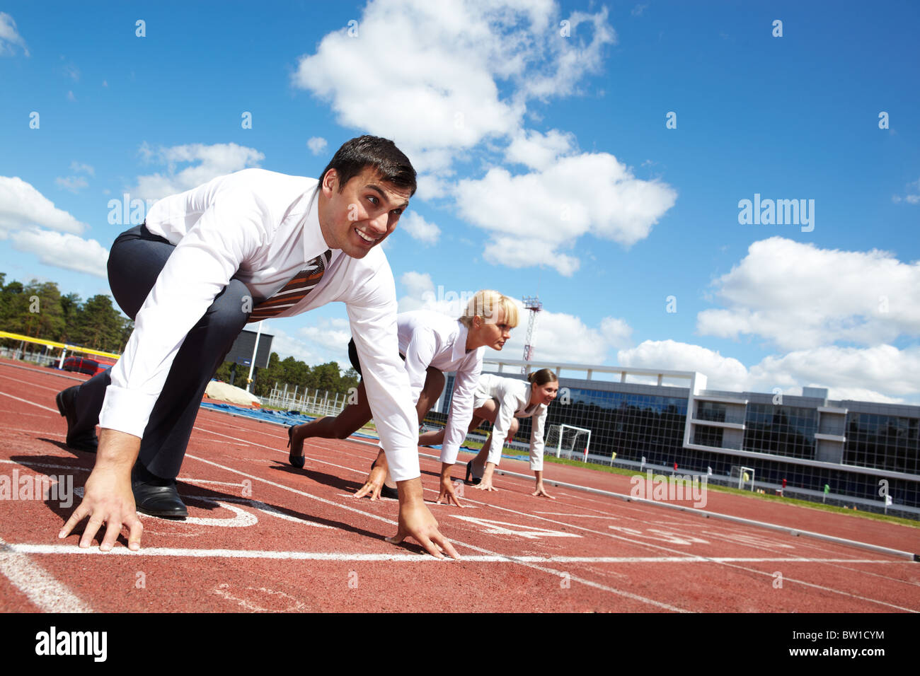 row of business people getting ready for race with man at foreground stock photo  32608904