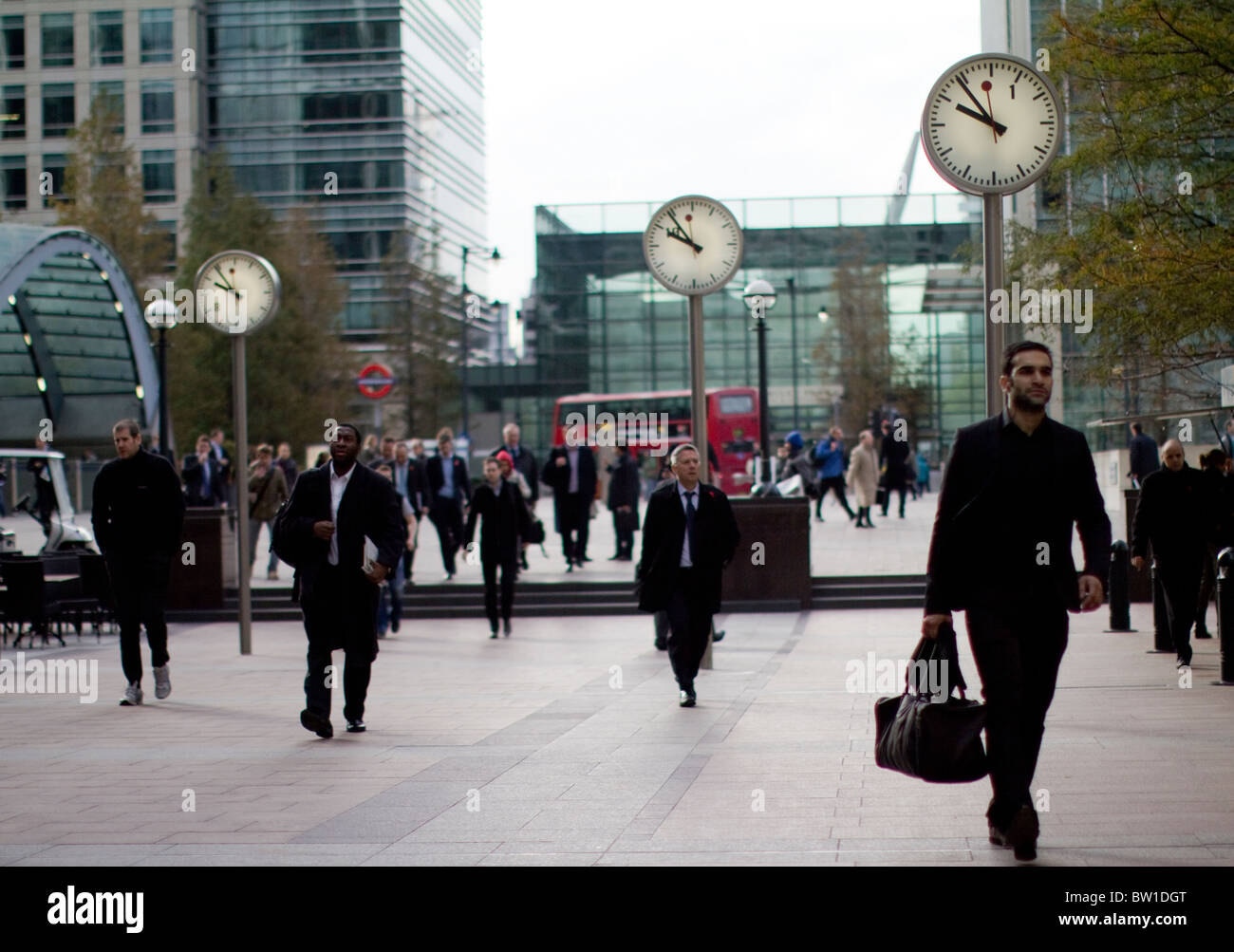 clocks outside canary wharf station with city workers , Six Public Clocks, Konstantin Grcic, Sculpture, Steel, Glass - Stock Image