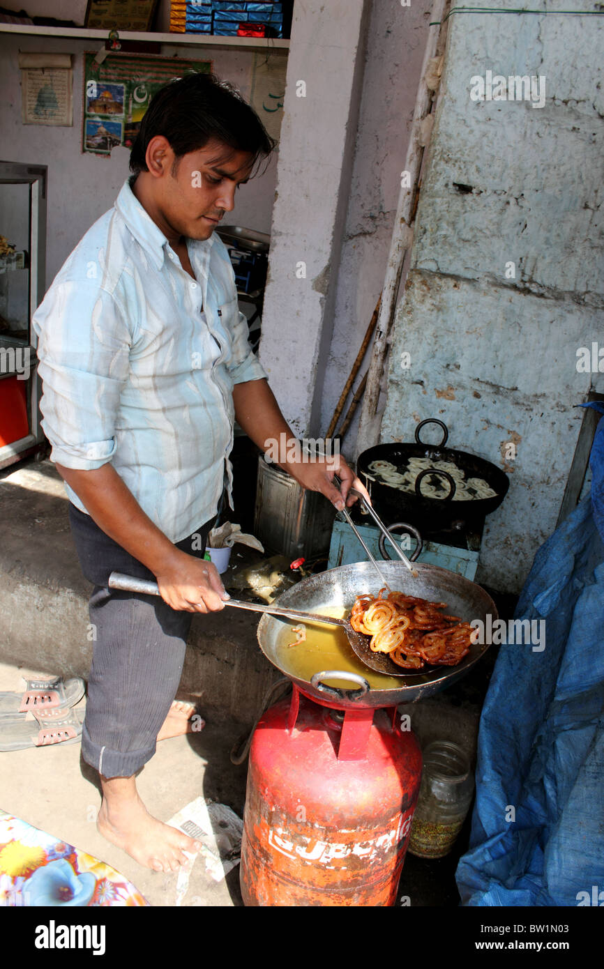 Man cooking (deep frying) Indian sweets (Jalebis) near Charminar Hyderabad India using a butane gas cylinder and - Stock Image