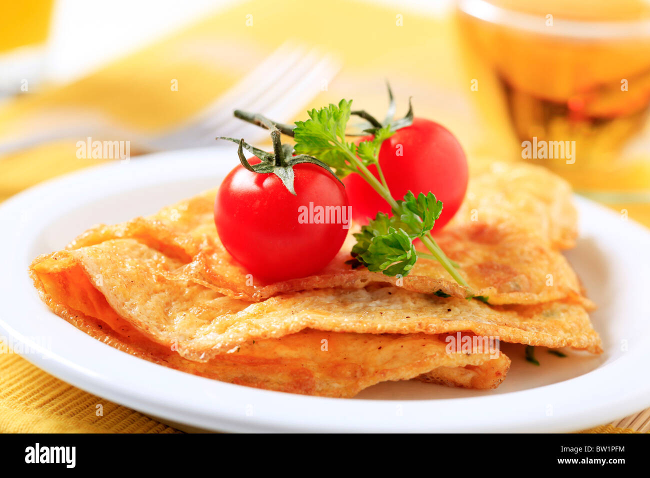 Omelets and two fresh tomatoes - Stock Image