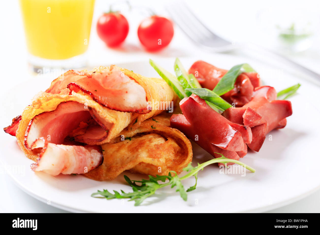 Omelet with bacon and sausages - Stock Image