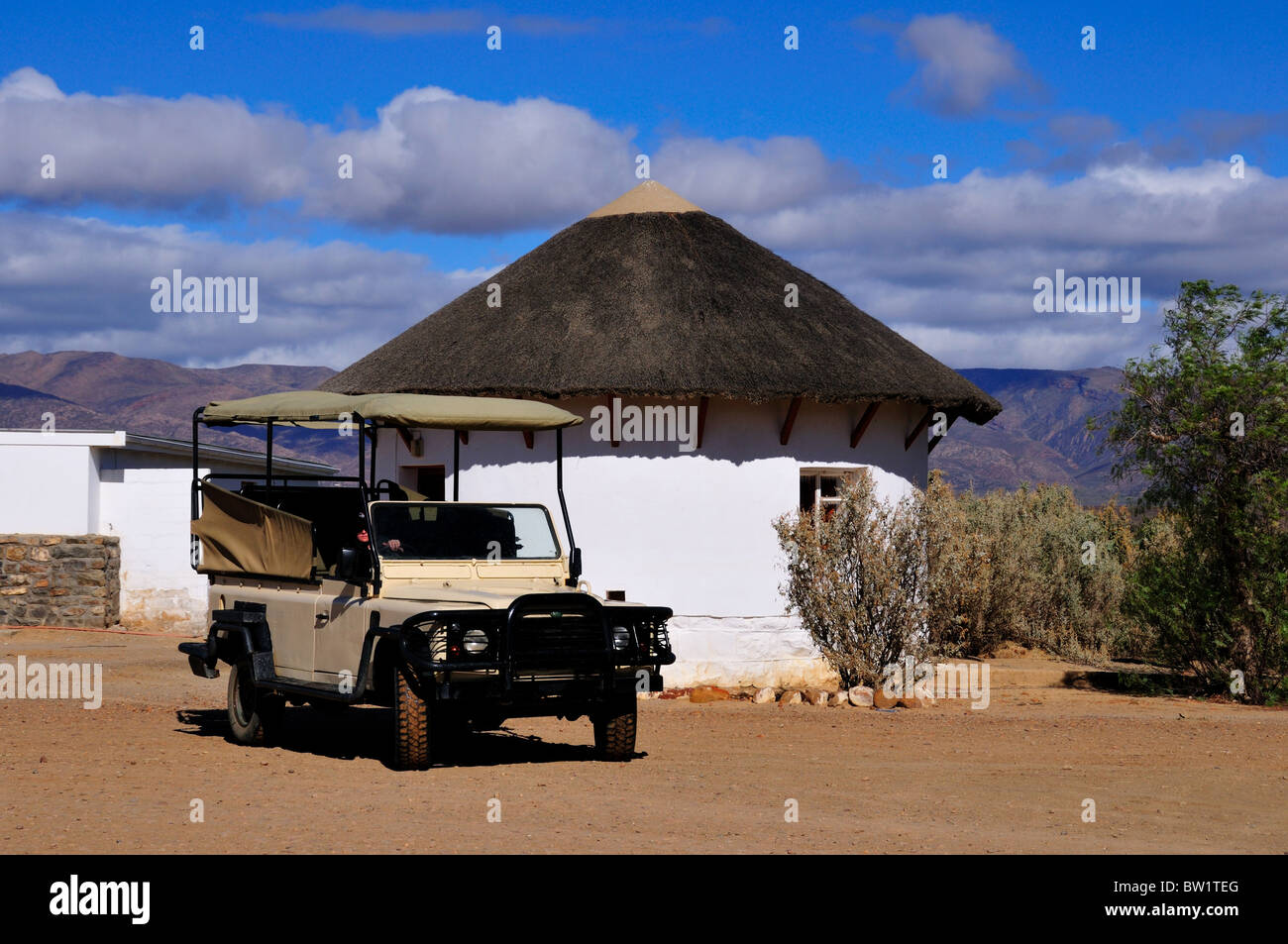 A Safari jeep parked in front of an African style hut. South Africa. - Stock Image