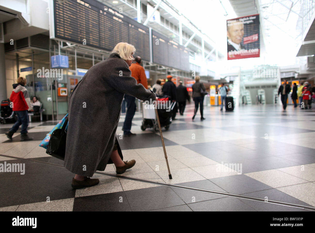 An old woman walking through the terminal of the Franz Josef Strauss Airport, Munich, Germany - Stock Image