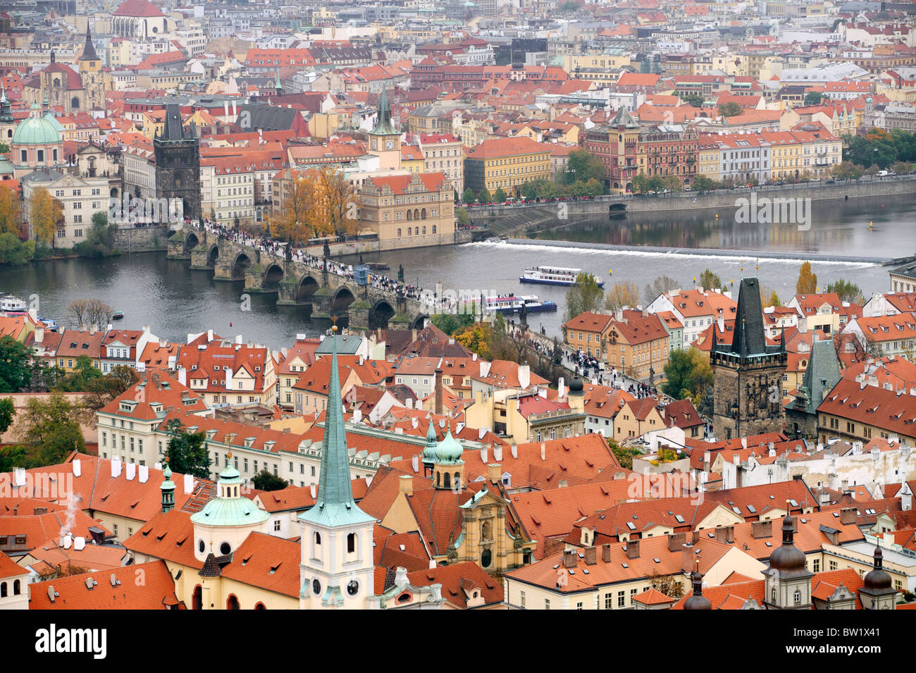 Charles Bridge Prague, crossing the river Vltava with cityscape and red tile roof as seen from the top of St Vitus - Stock Image