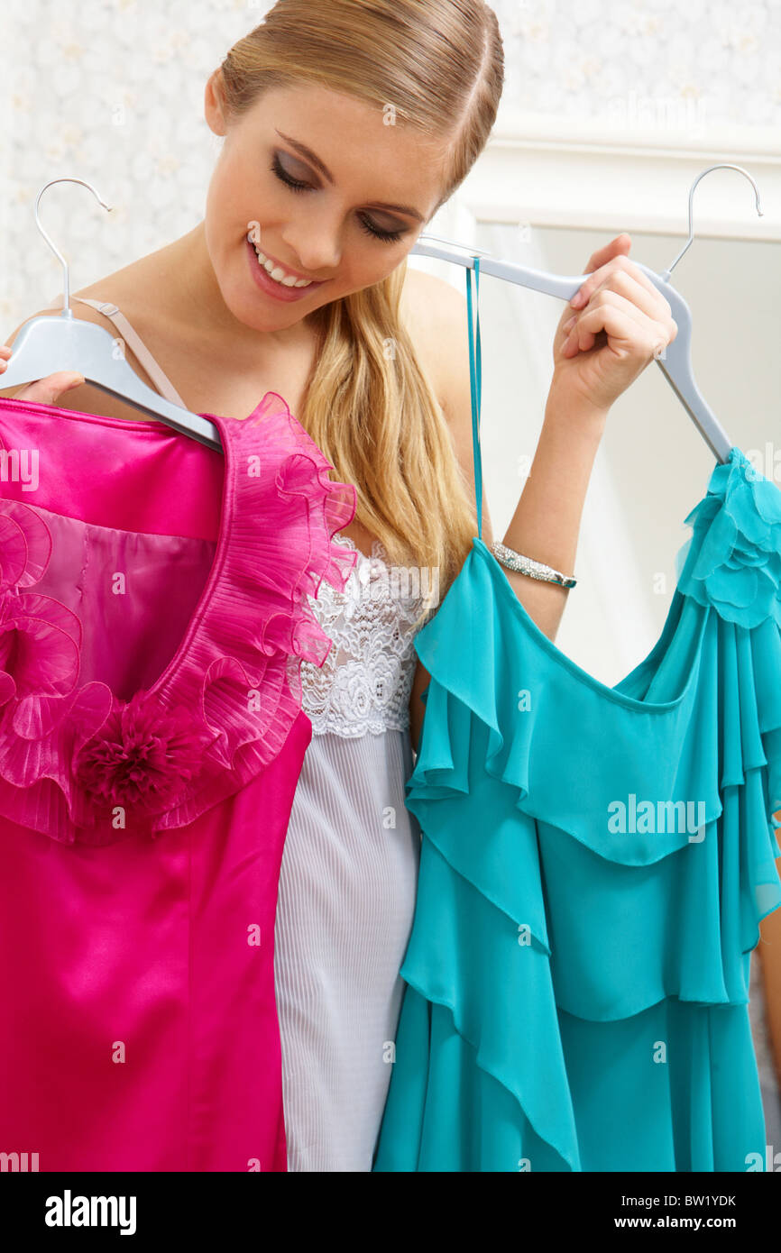 Image of pretty female looking at smart dresses while choosing a right one - Stock Image