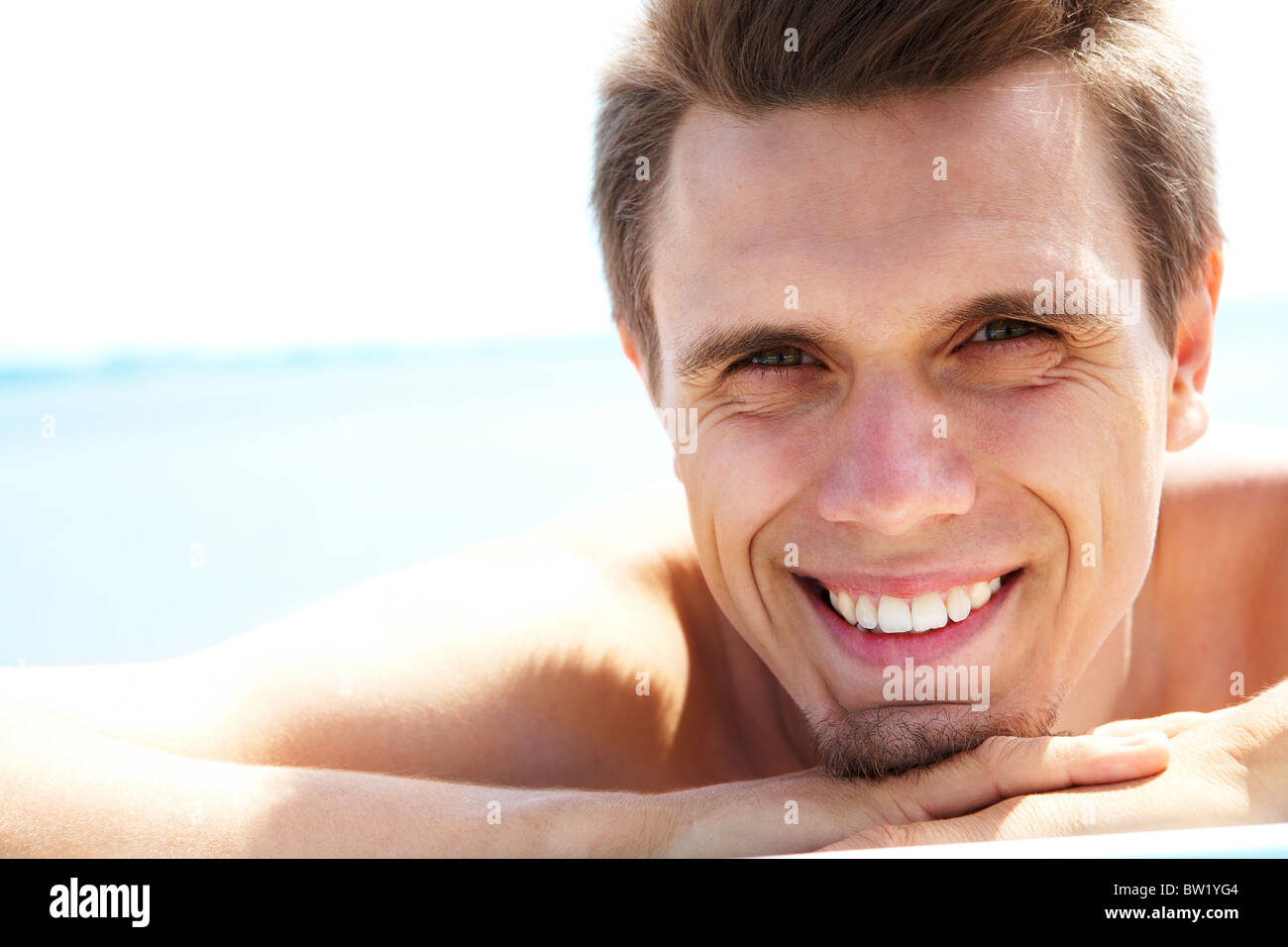 Photo of smiling guy looking at camera while sunbathing - Stock Image