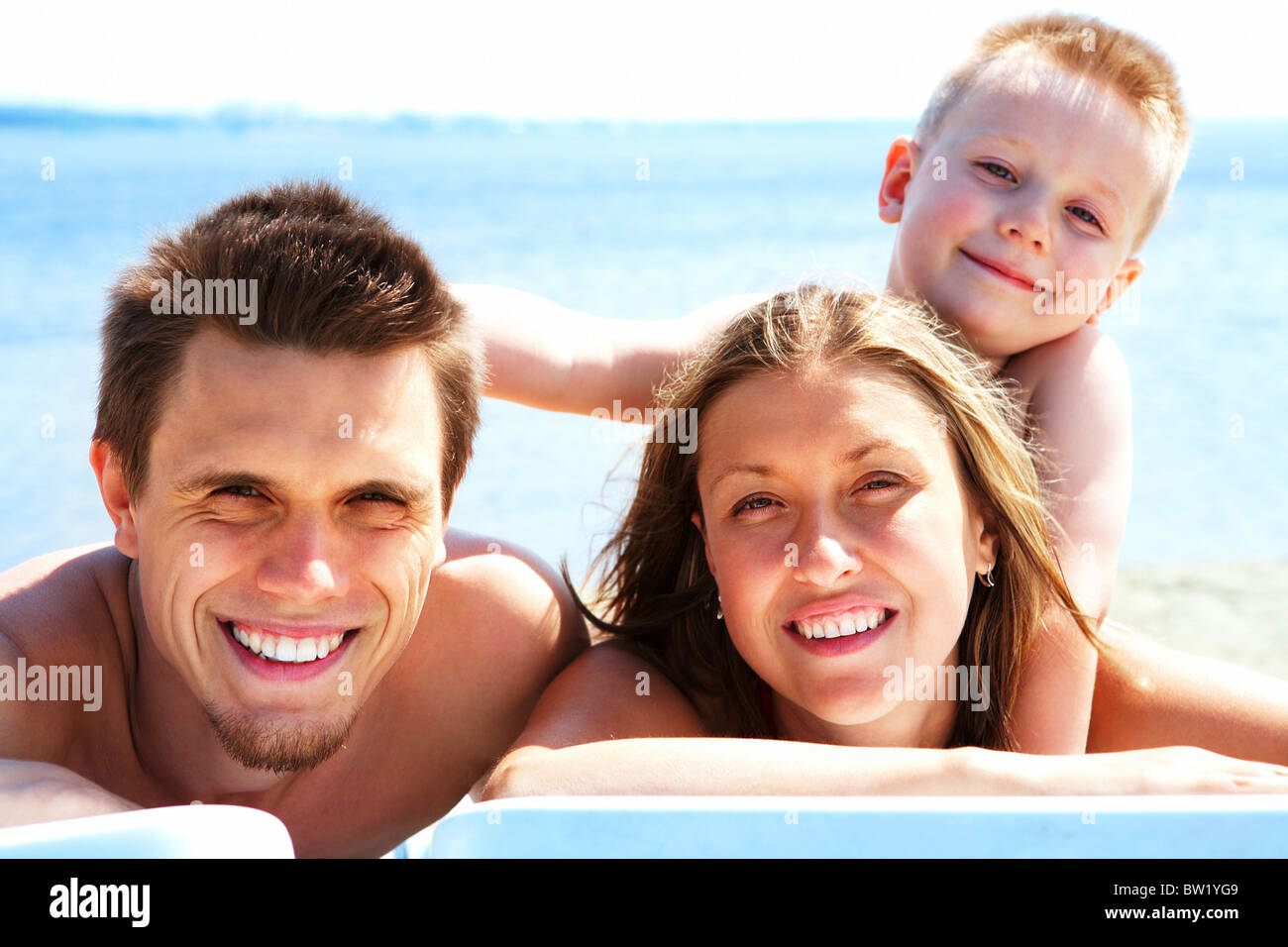 Photo of smiling family looking at camera while sunbathing - Stock Image