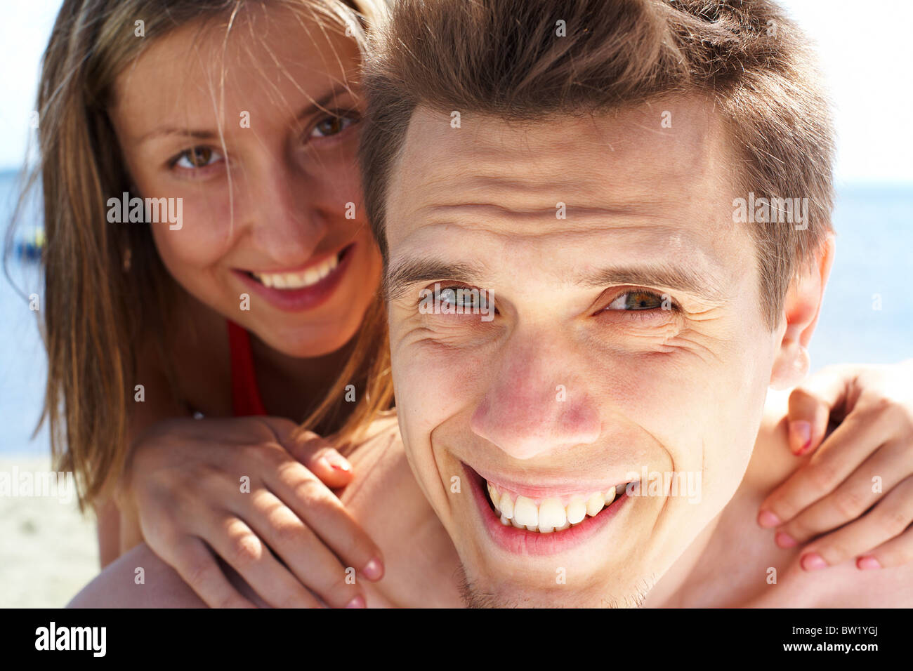 Photo of smiling guy looking at camera while pretty woman behind embracing him - Stock Image