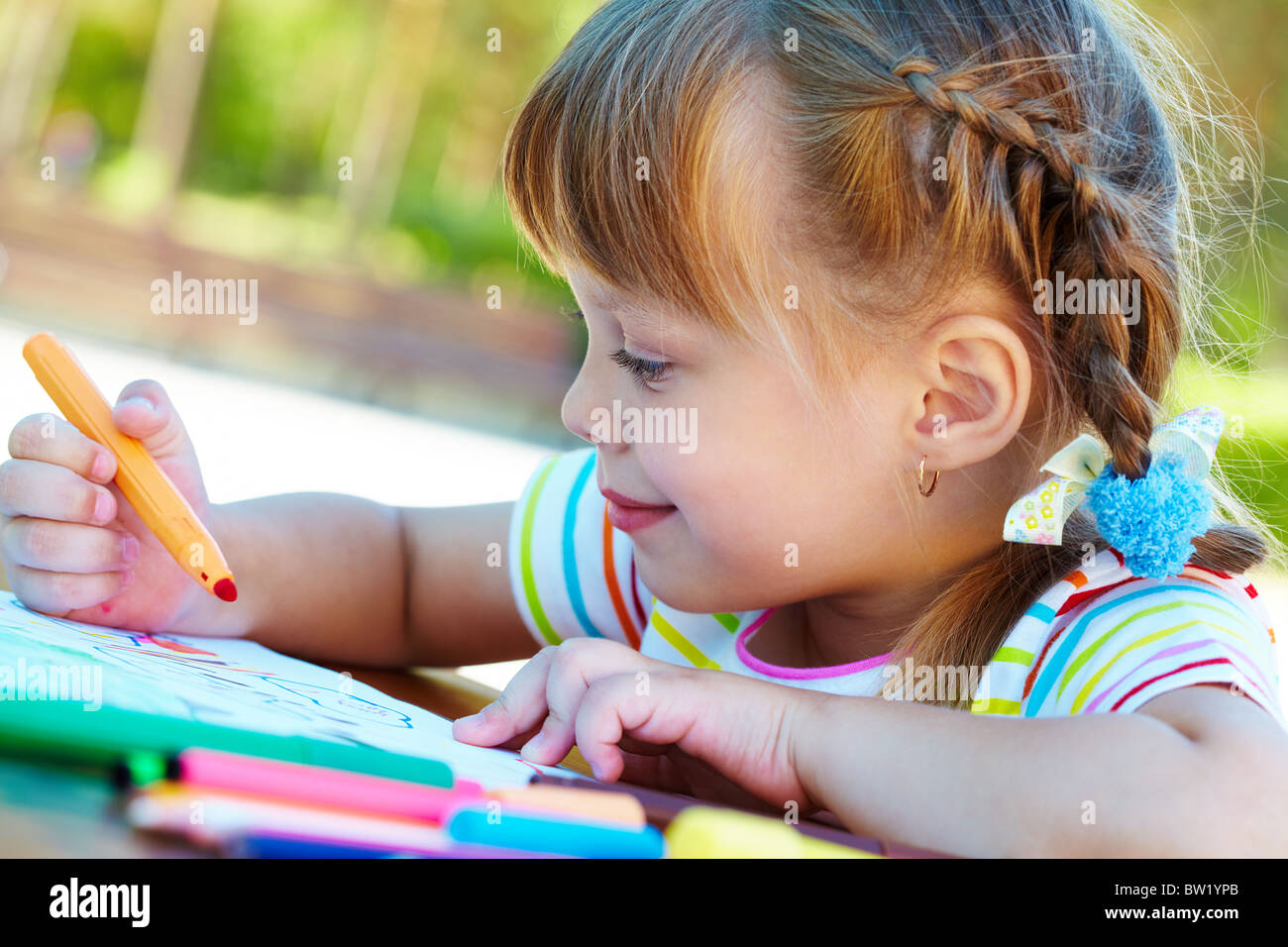 Portrait of cute girl interested in drawing with highlighters - Stock Image