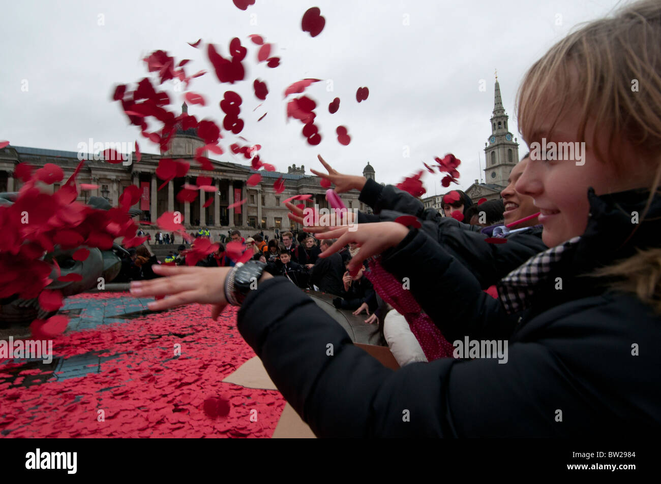 November 11th 2010. Remembrance Day Trafalgar Square.Young girls throwing poppies into the fountains. - Stock Image