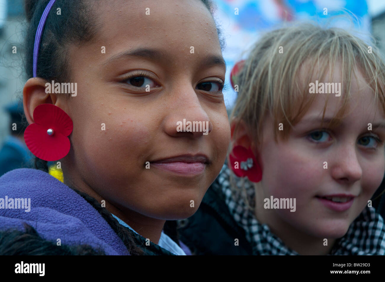 November 11th 2010. Remembrance Day Trafalgar Square. Two young girls wear poppies on their ears - Stock Image