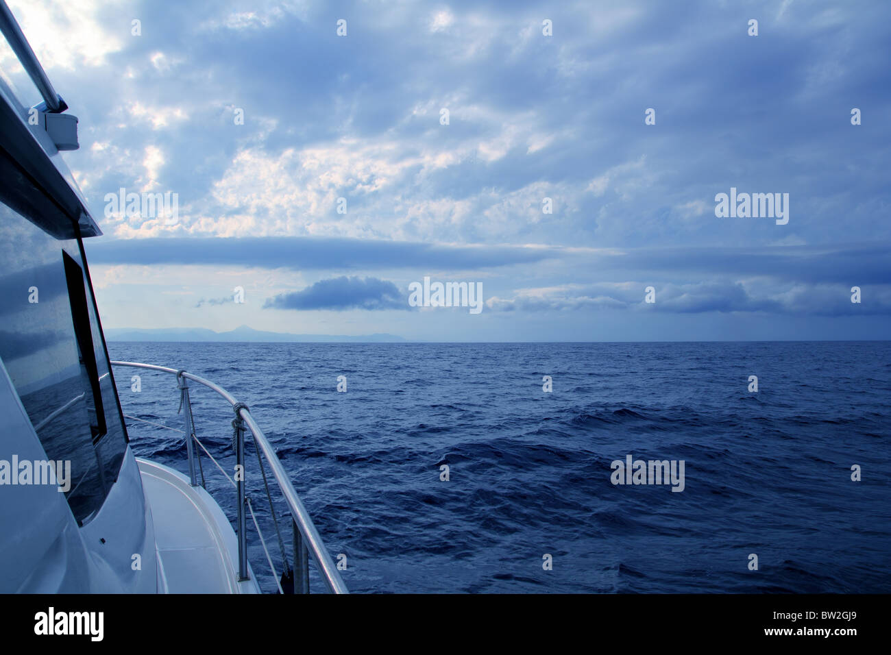 Boat sailing in cloudy stormy day blue ocean sea, yacht side view - Stock Image