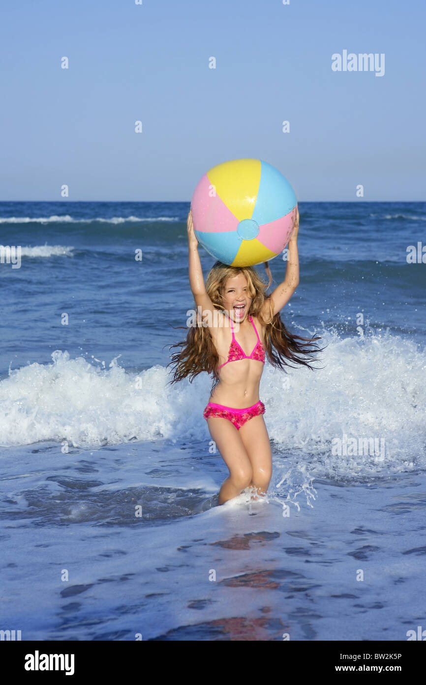 e1a1a114aa Beach little girl colorful ball vacation playing in blue sea - Stock Image