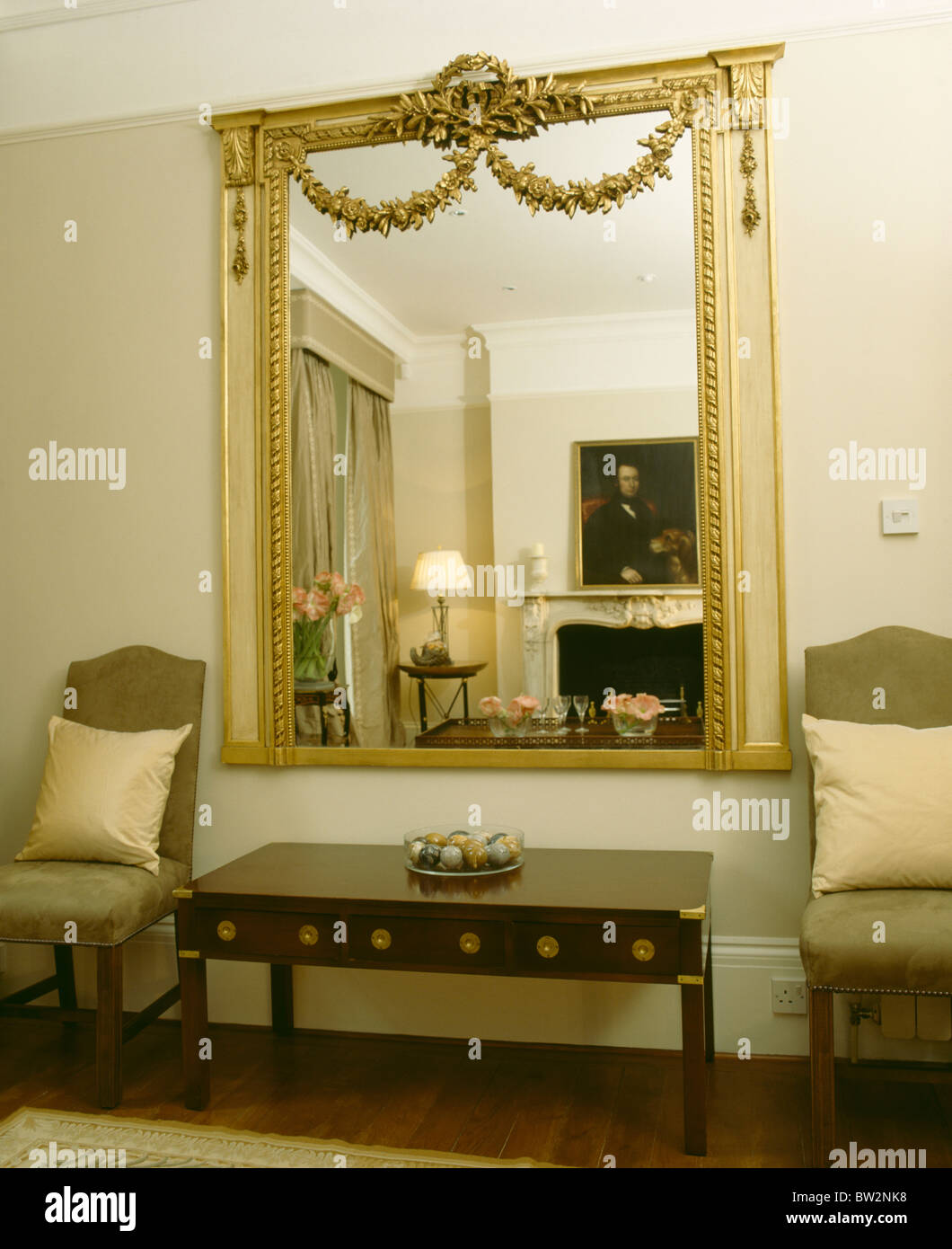 Large ornate gilt antique mirror on wall above console table in ...