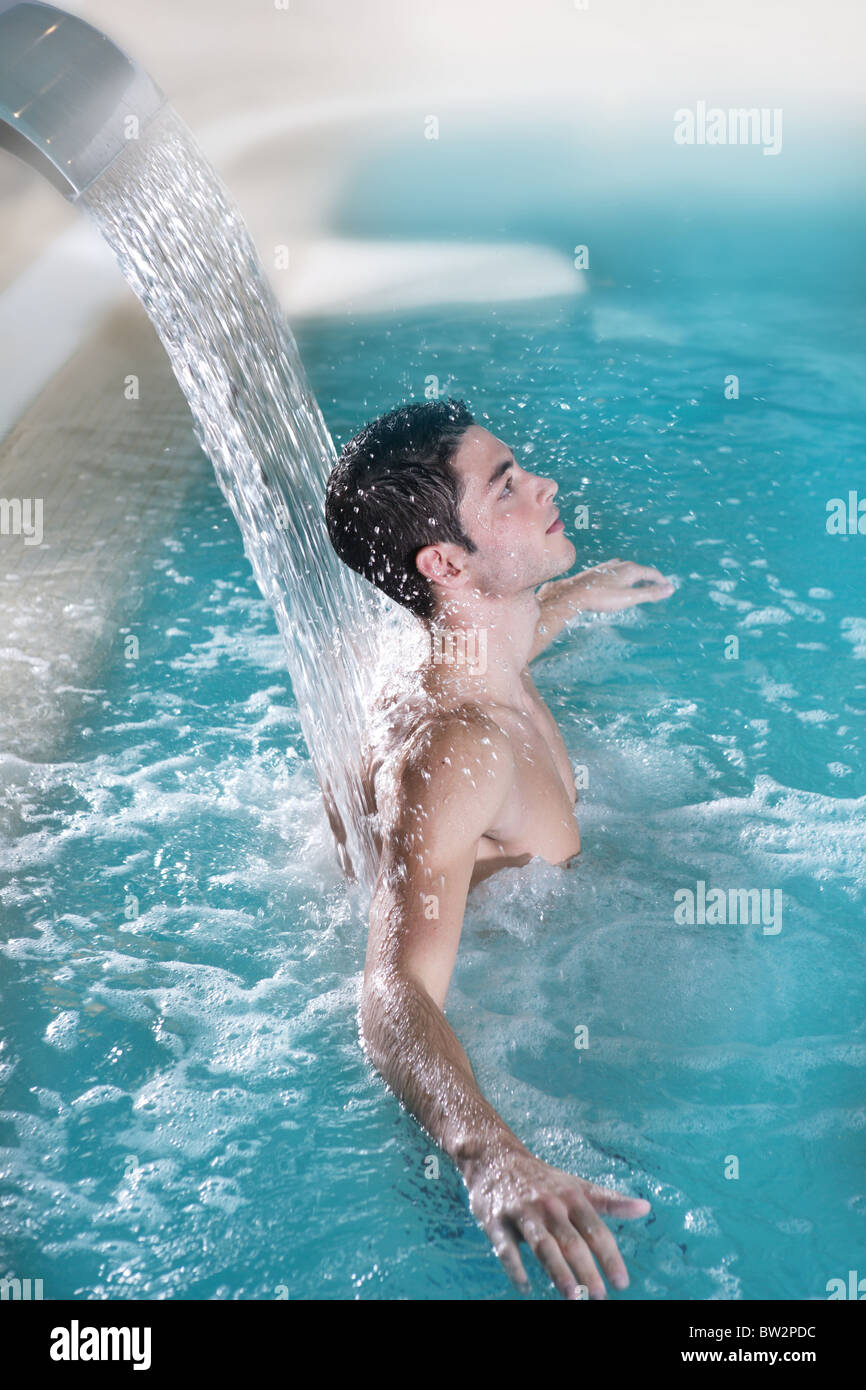 spa hydrotherapy man waterfall jet turquoise swimming pool water - Stock Image