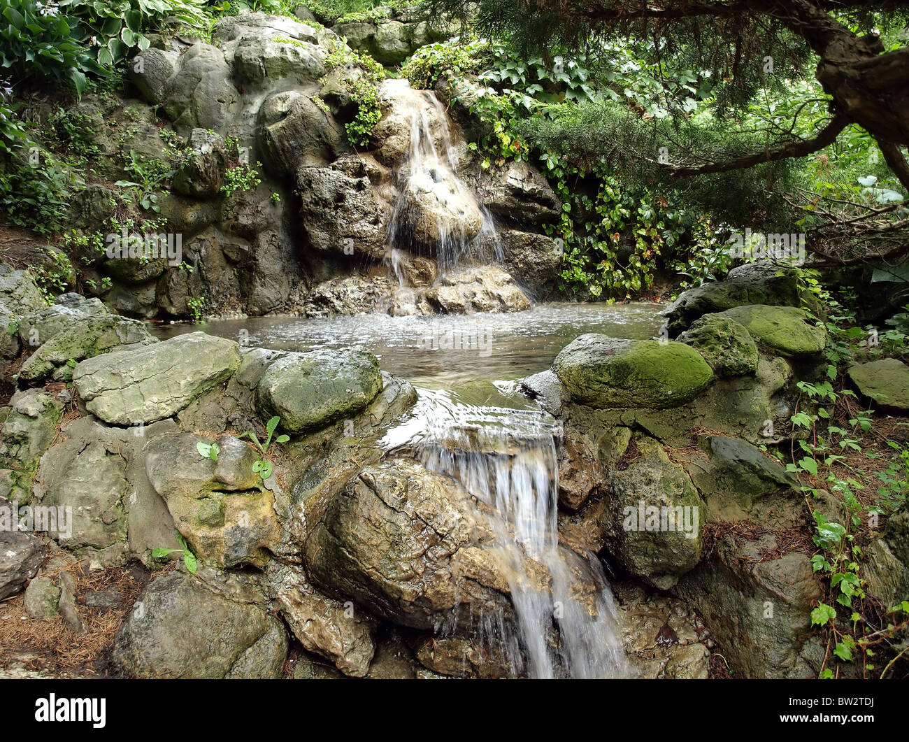 Picture of small waterfall in summer garden - Stock Image