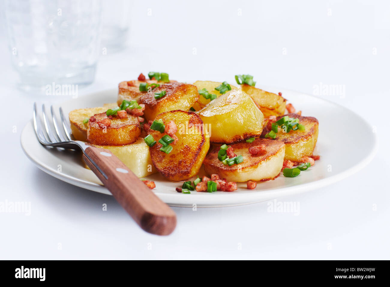 Image of fried potatoes with green leek - Stock Image
