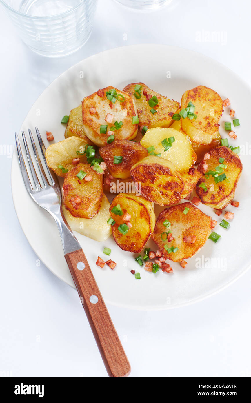 Above view of fried potatoes with green leek - Stock Image