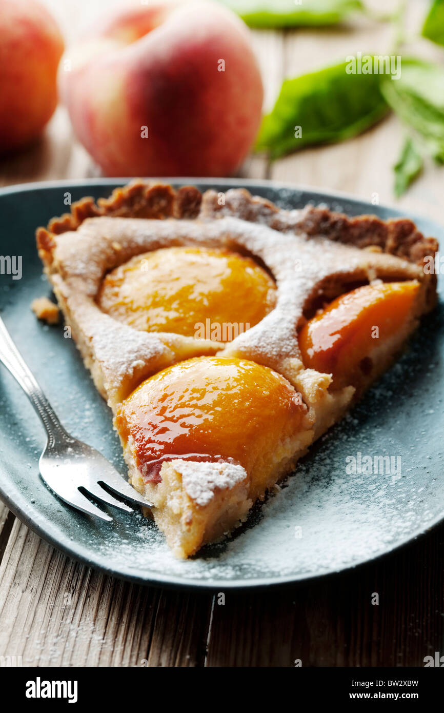 slice of homemade french peach tart, made with fresh poached peaches - Stock Image