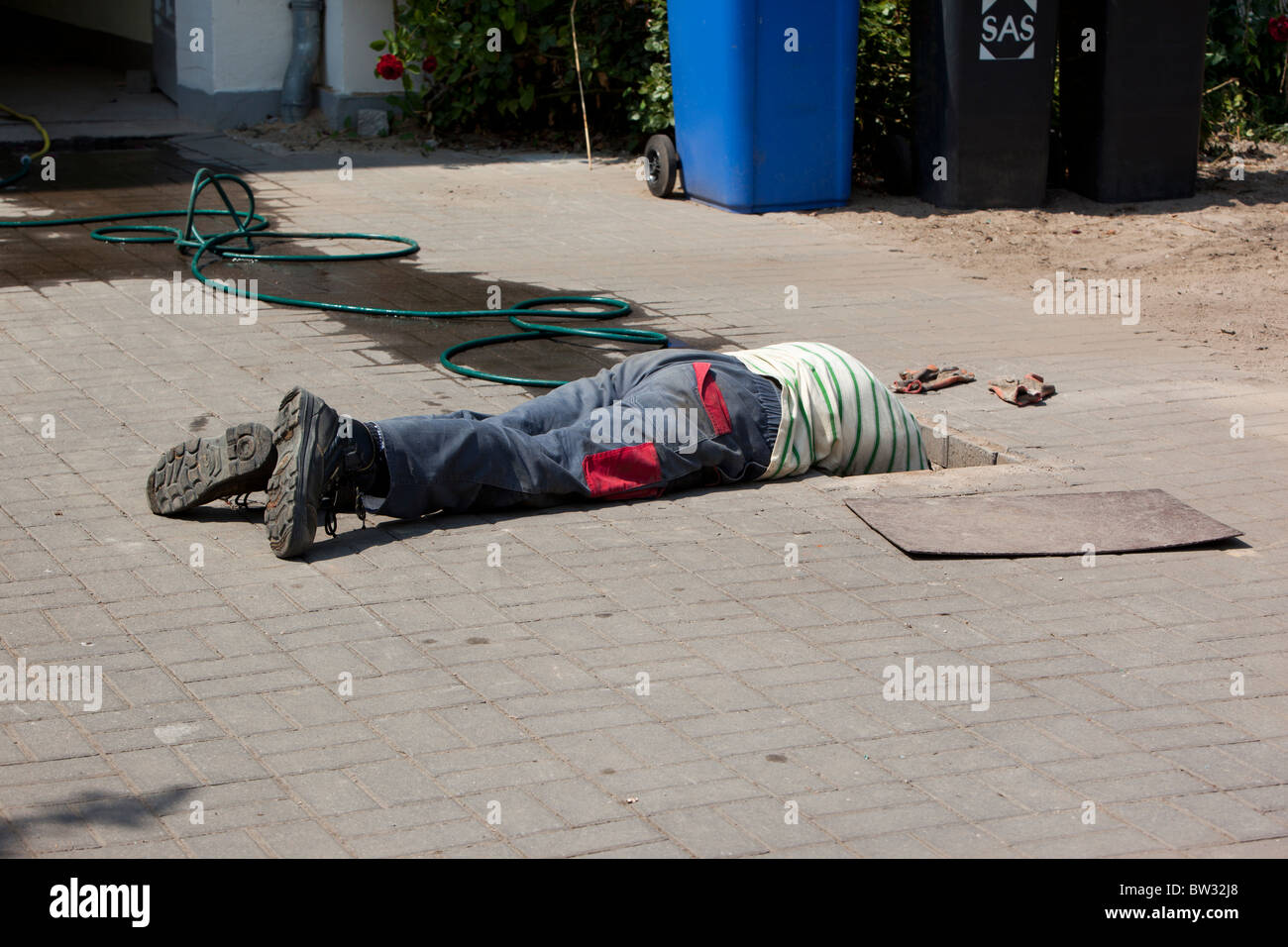 A man looks into a hole in the street - Stock Image