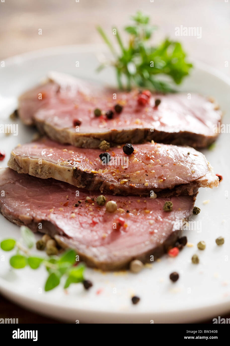 slices of juicy roast beef with herbs and pepper - Stock Image