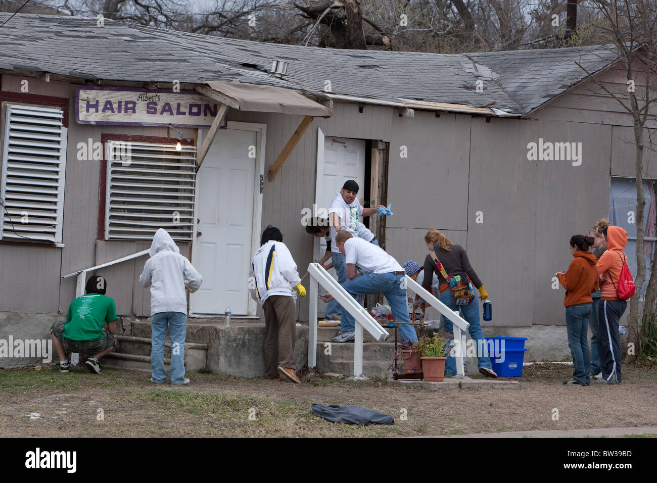 College students belonging to Filipino-American campus group paint a run-down house in a low-income neighborhood - Stock Image