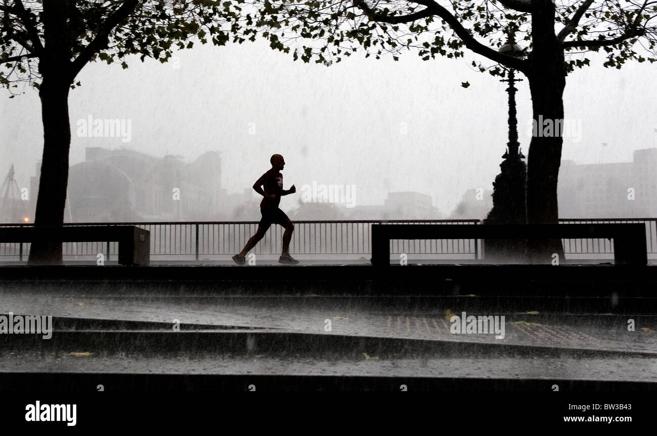 A rainy day in London, Britain. A running man jogs during heavy rain storm along the embankment, central London. - Stock Image