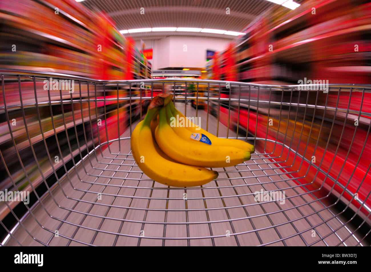 Bananas in supermarket trolley cart with motion blur taken with fisheye lens - Stock Image