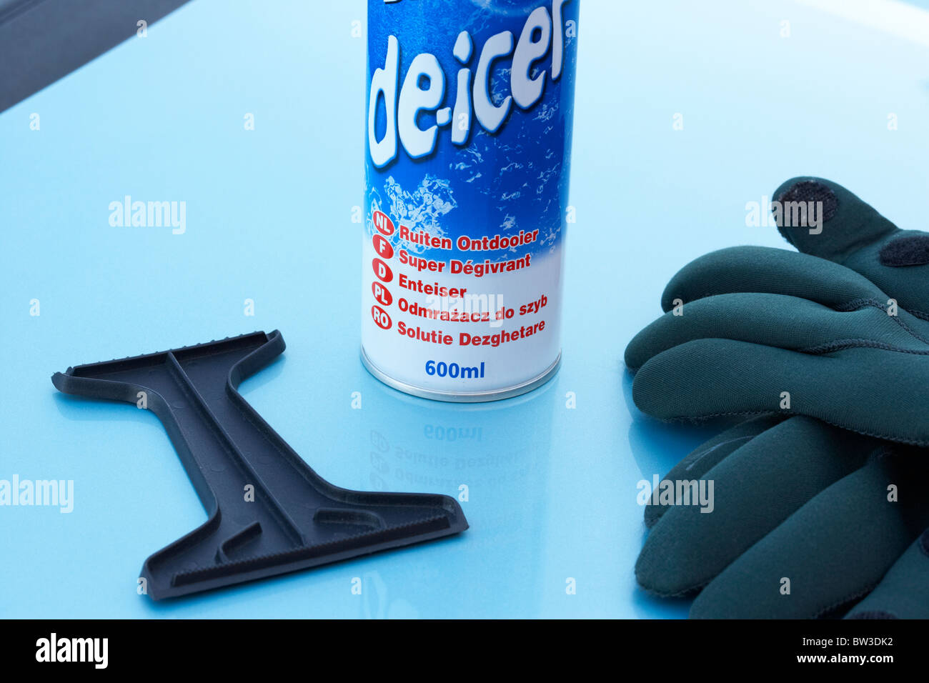 can of de-icer ice scraper and gloves on a car bonnet - Stock Image