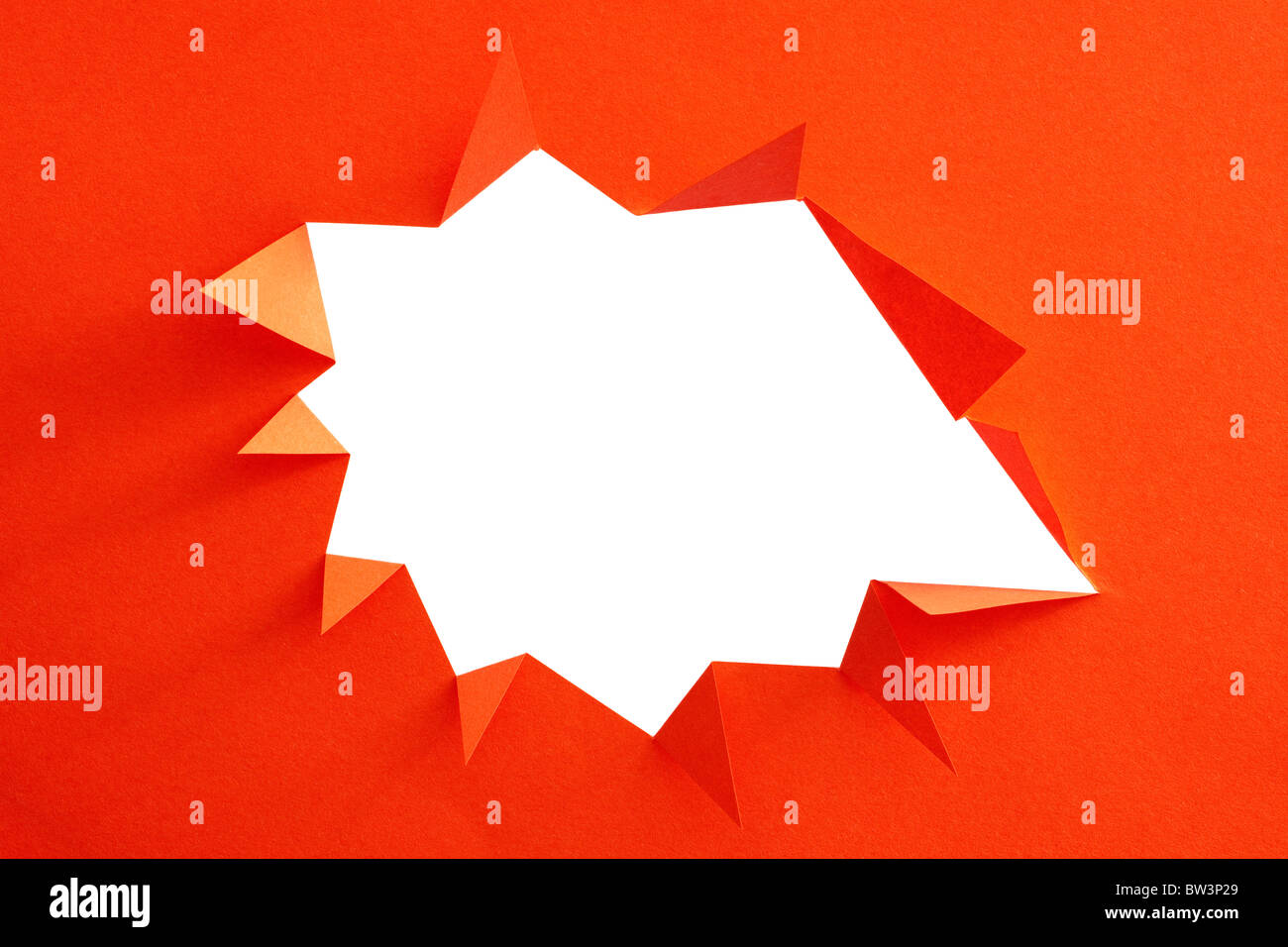 Red piece of paper with jagged edged white hole - Stock Image