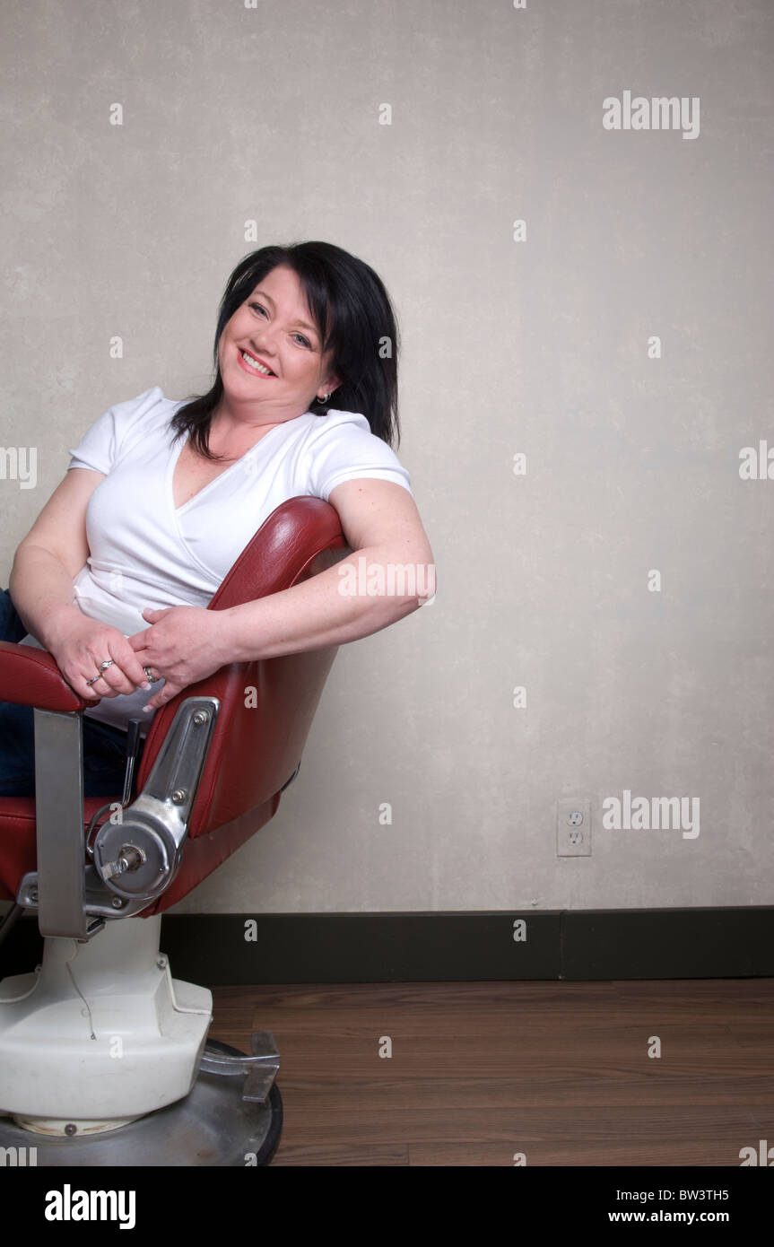 35 year old Caucasian woman sitting in barber's chair - Stock Image