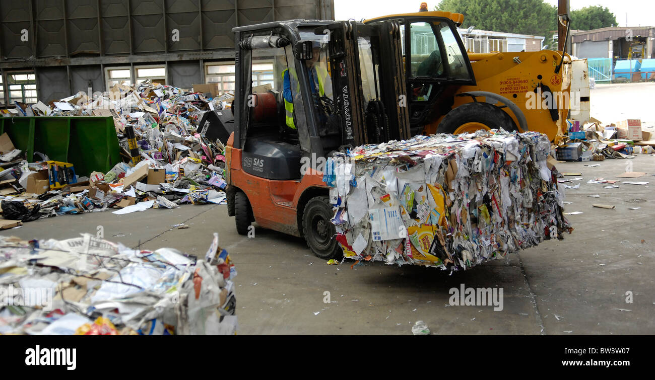 Newspapers, cardboard, magazine and paper is loaded after being bailed prior to recycling at the Folkestone Waste - Stock Image