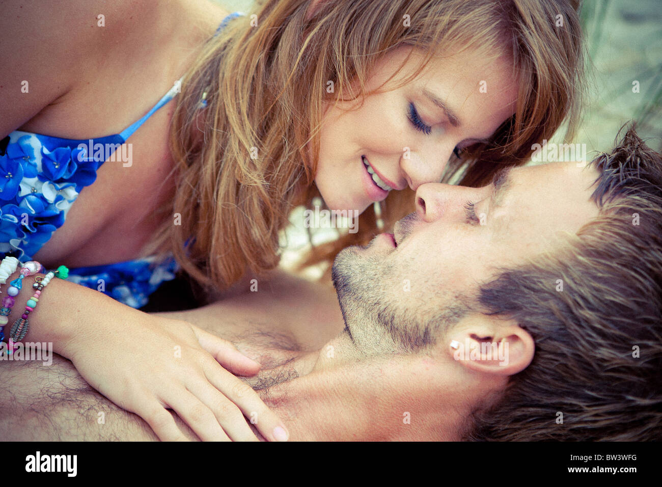Young couple lie embracing - Stock Image