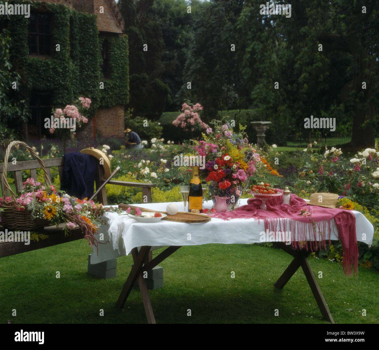country garden in summer with table on lawn set for lunch with white