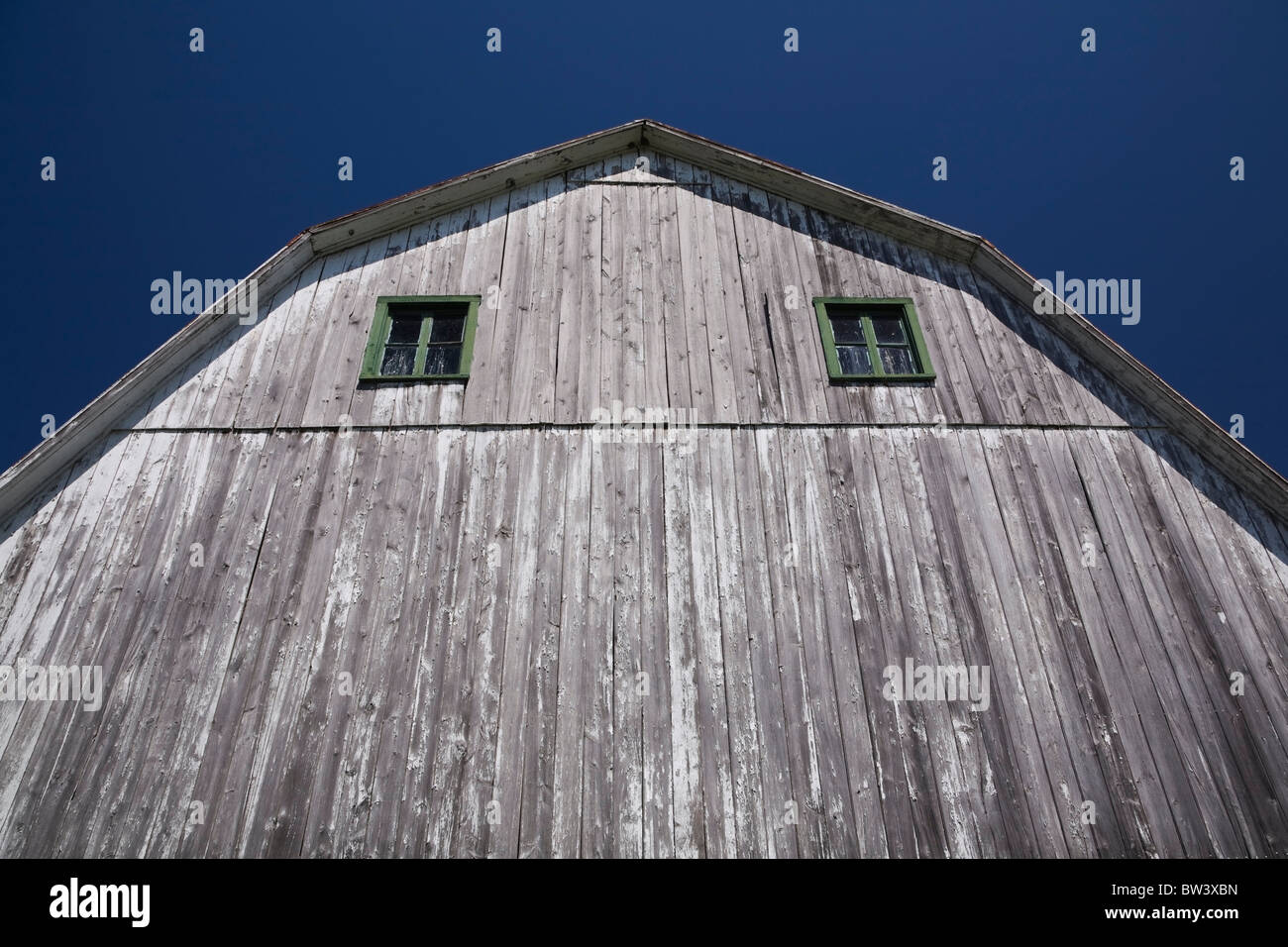 Partial view of the side of an old Mansard style wooden barn, Laval, Quebec, Canada - Stock Image