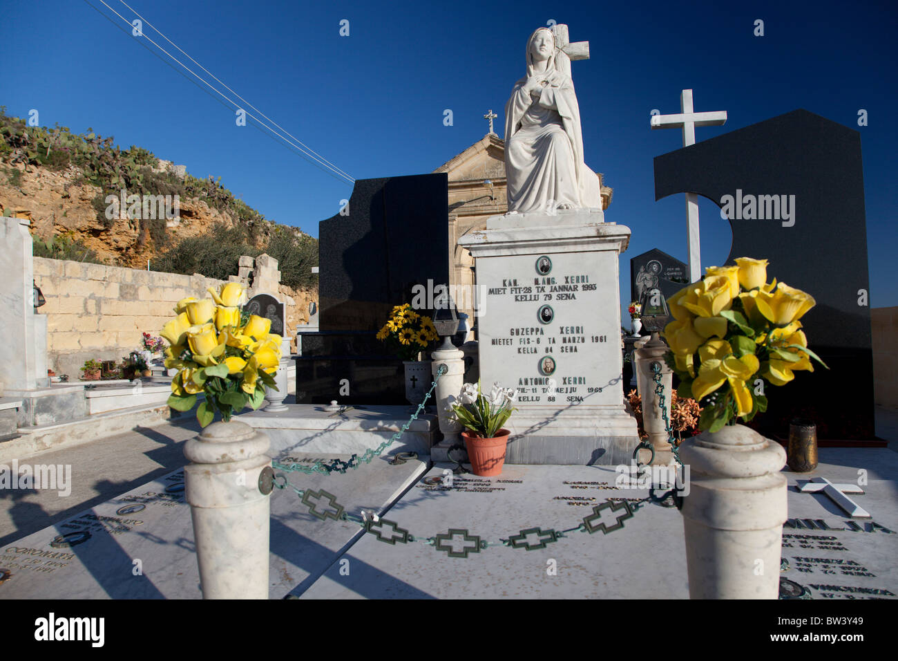Ornate baroque tombstones adorn graves in cemeteries in the Maltese Islands. - Stock Image