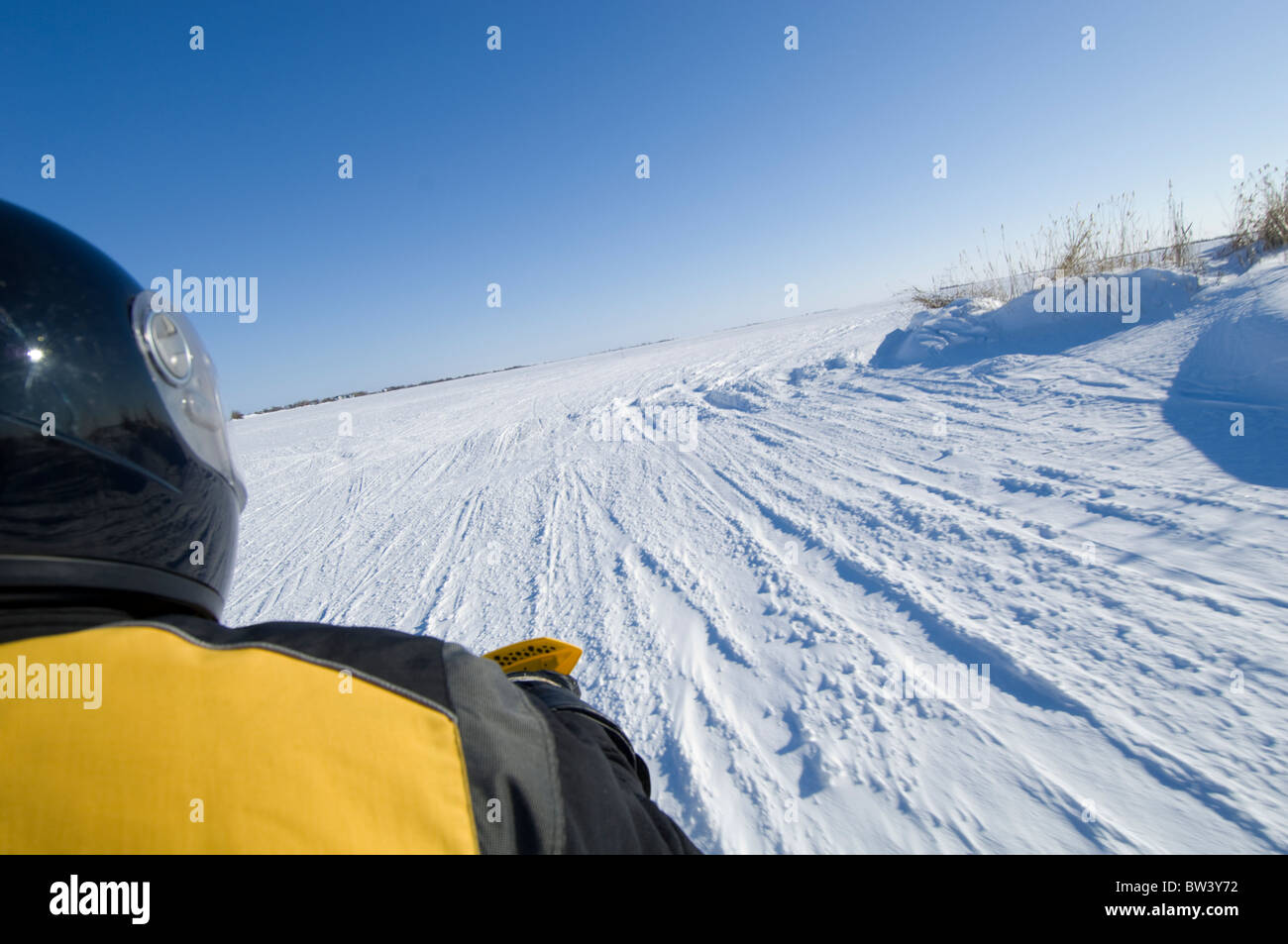 Snowmobiler driving on frozen lake in Manitoba, Canada - Stock Image