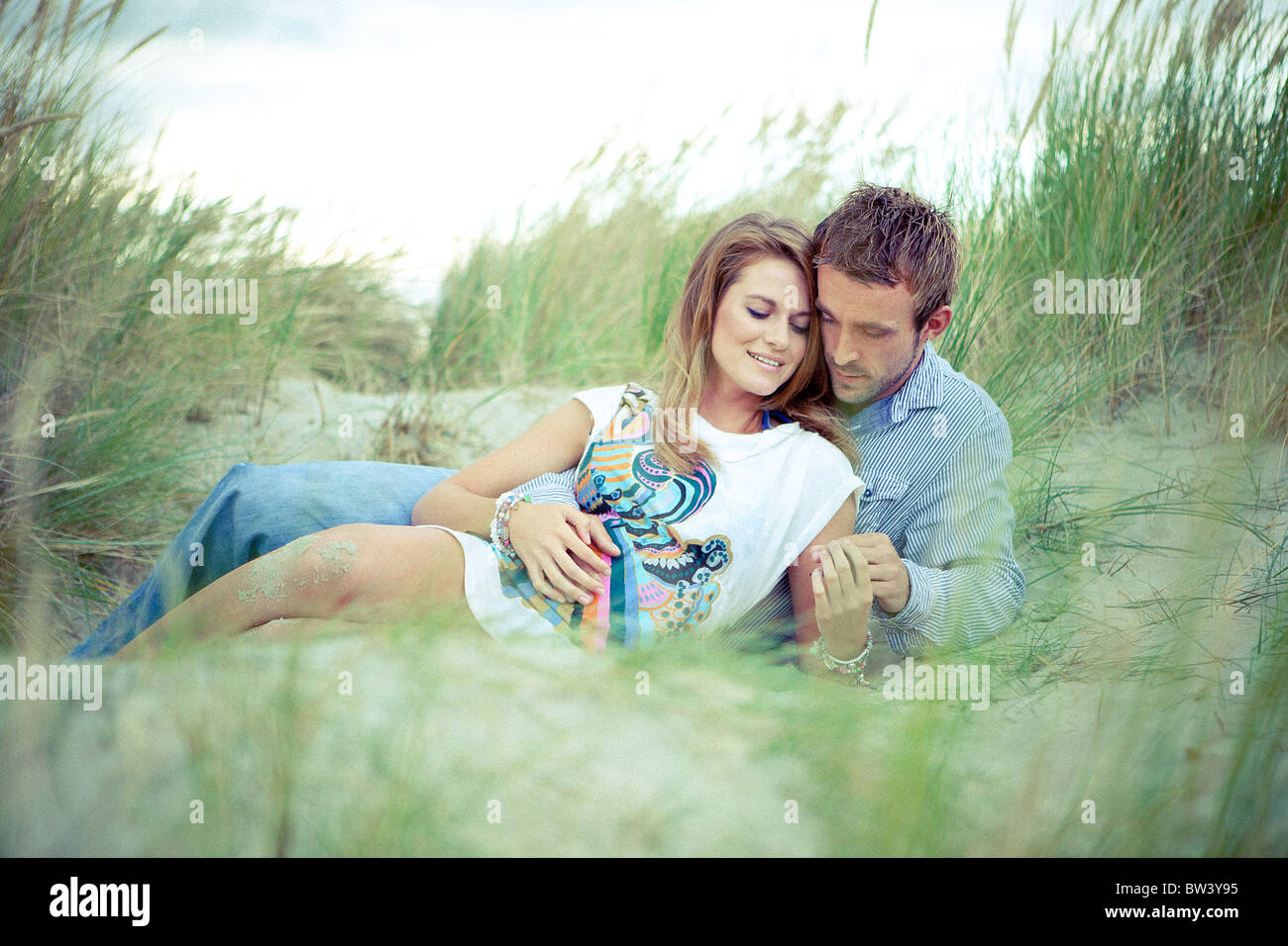 Young couple cuddle on sand dunes - Stock Image