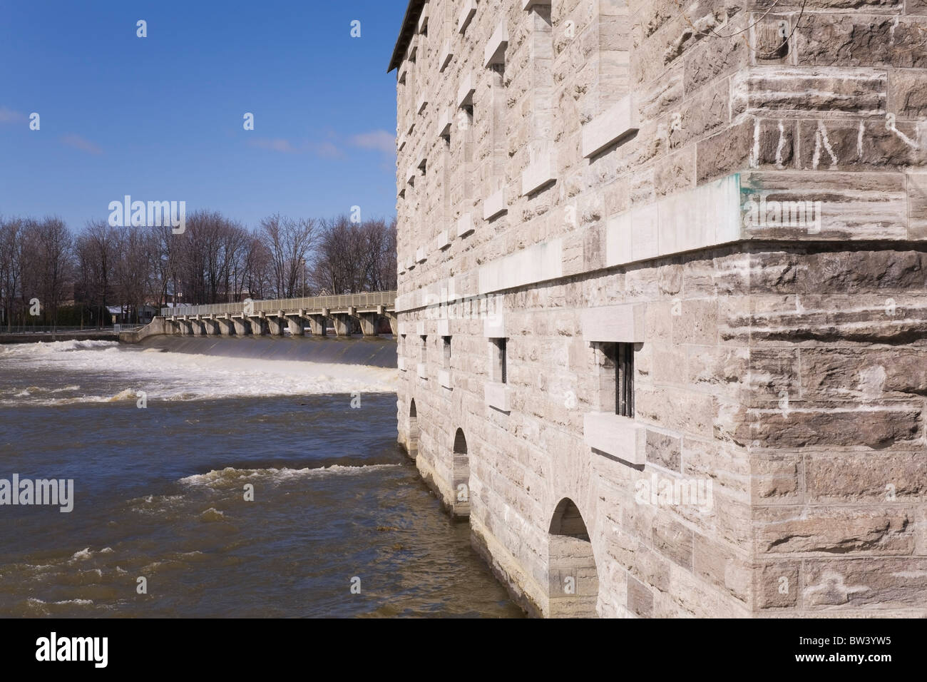 Partial view New Mill and Water Flow Control Dam on Mille-Iles River at Springtime, Old Terrebonne, Lanaudiere, - Stock Image