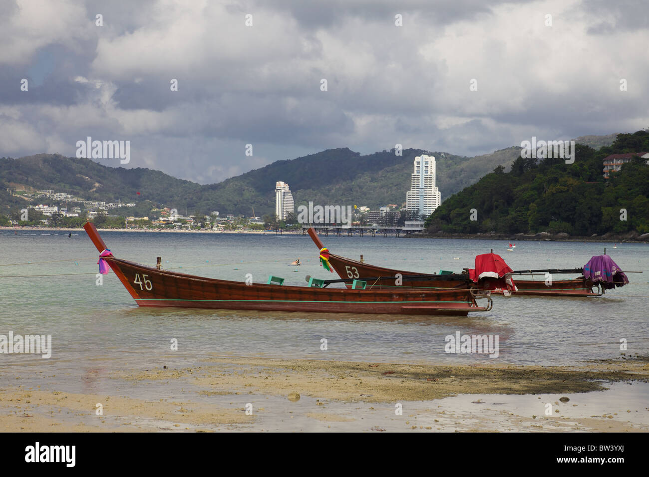 Long tail boats with Patong beach in the background, Phuket, Thailand - Stock Image