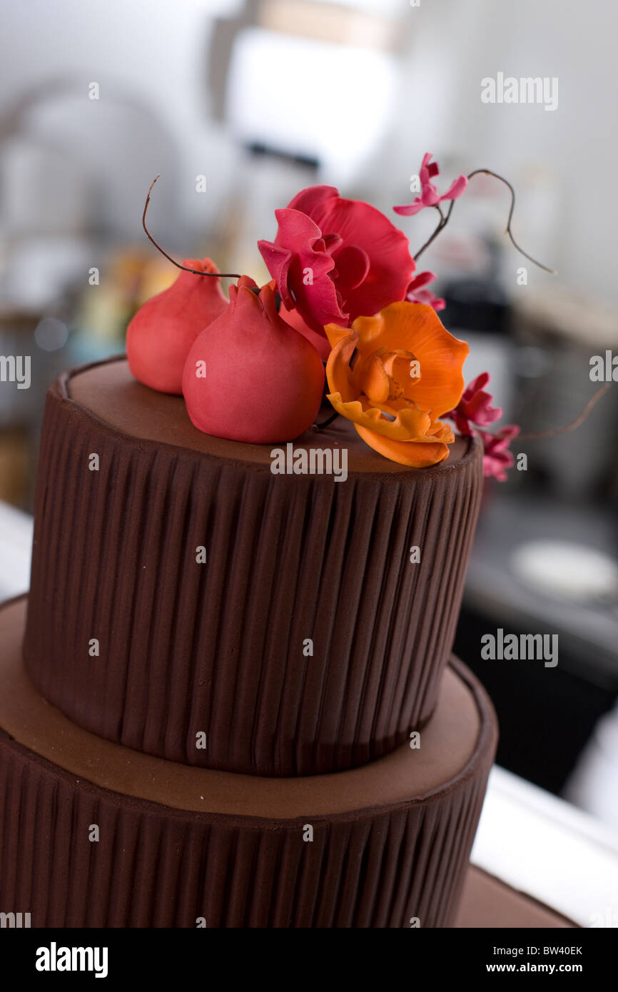 Top of tiered cake, brown with pink and orange flower decorations - Stock Image