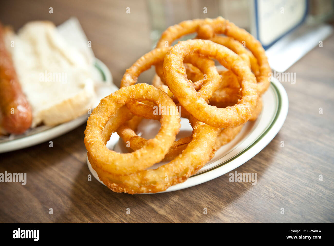 Plate of onion rings and hot dog on wooden countertop - Stock Image