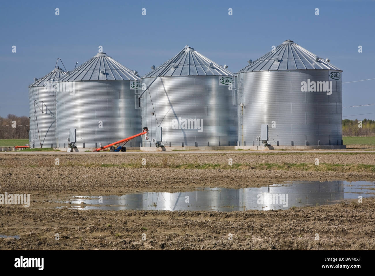 Grain storage bins in an agricultural field, Lanaudiere, Quebec, Canada - Stock Image