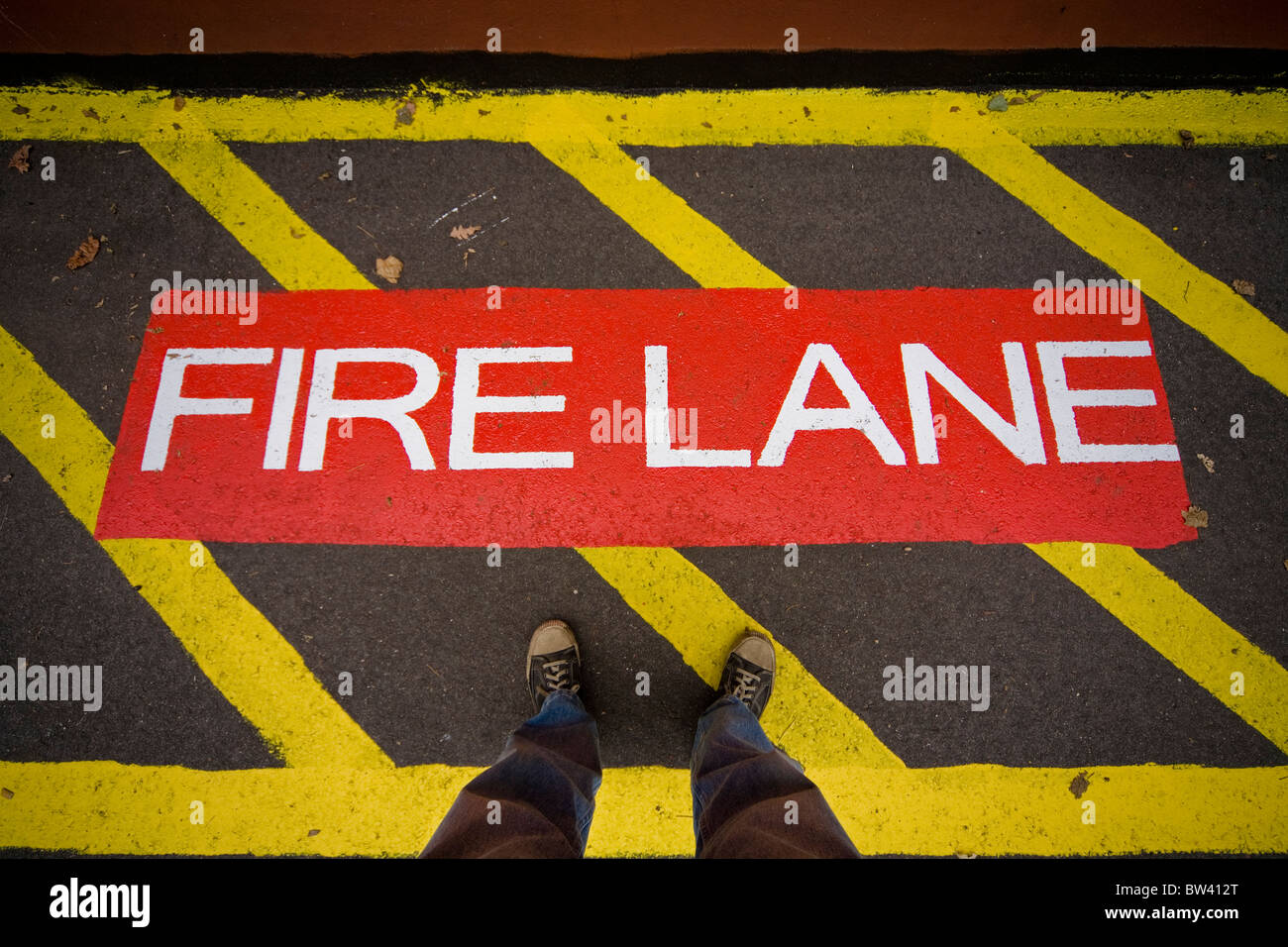 Man standing in a section of a driveway labeled 'Fire Lane' - Stock Image