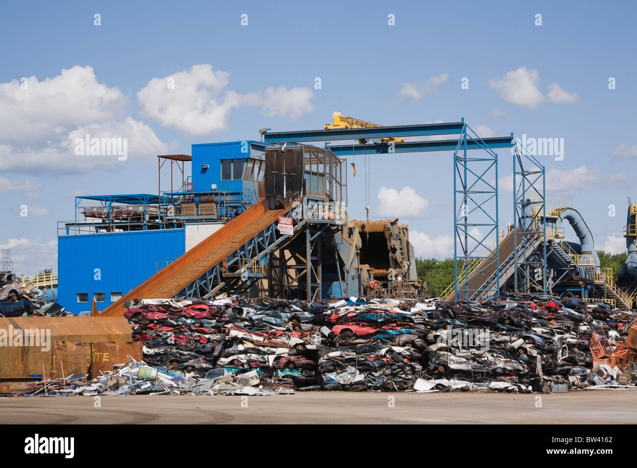 Crushed automobiles and shredder at a scrap metal recycling junkyard, Quebec, Canada - Stock Image
