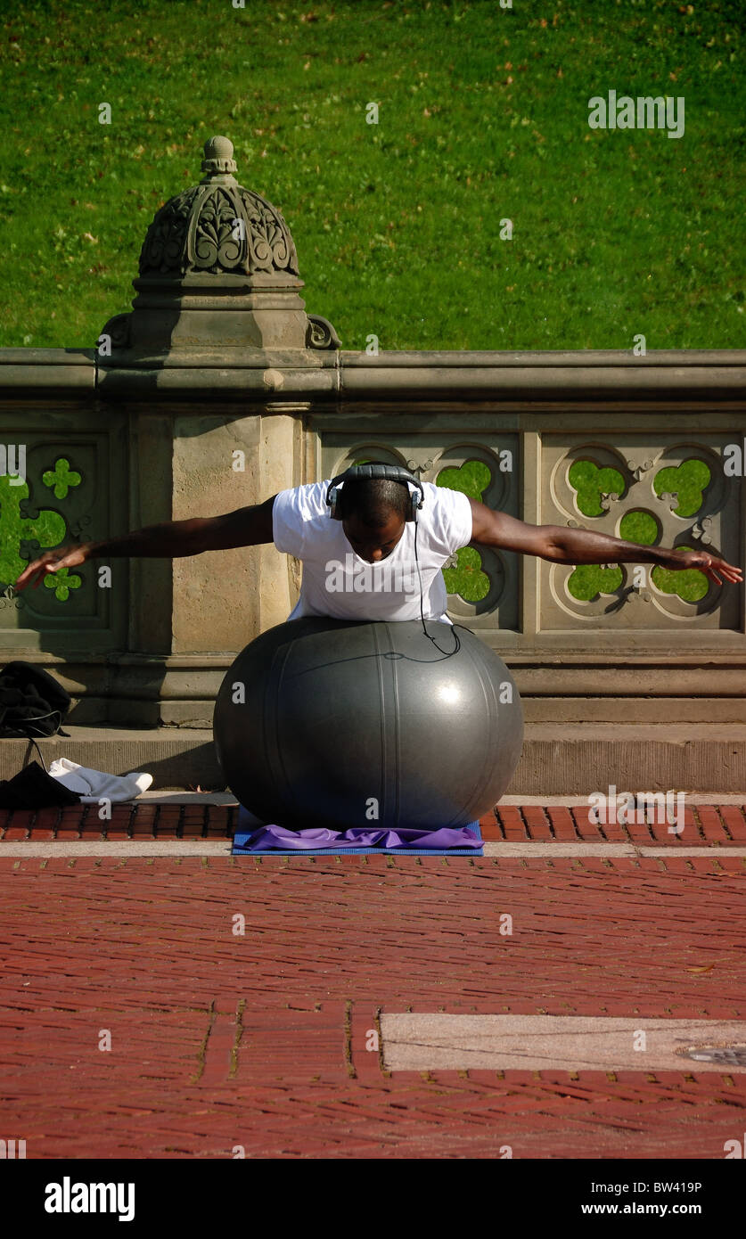 A physically fit African American young man wearing headphones exercises with an exercise in Central Park, New York - Stock Image