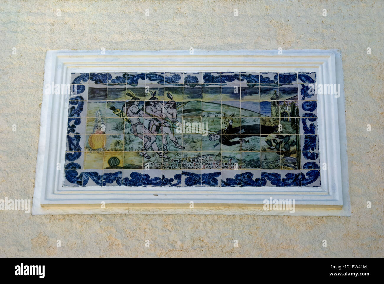 Tile mosaic art above mission church door in Baja, Mexico, depicting Indians revolting against priests who are against - Stock Image
