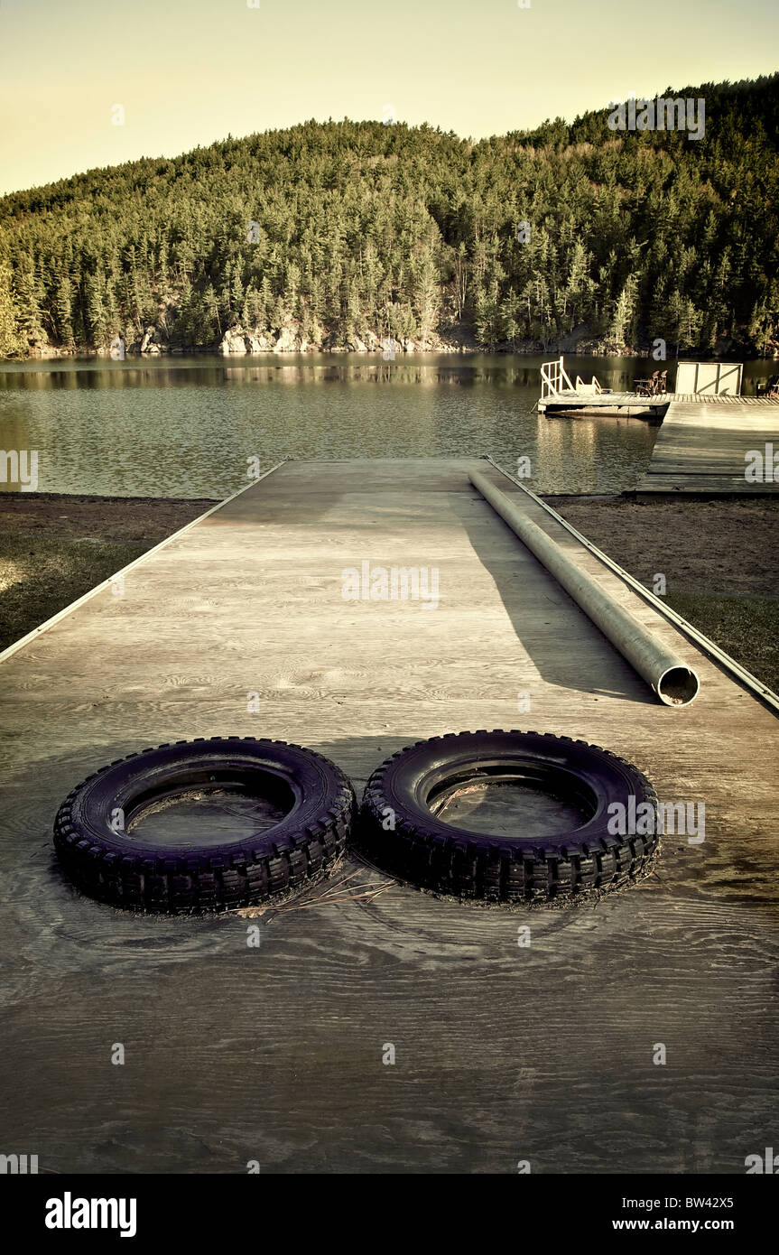 Tires on a beached floating pier near a lake, Mattawa, Ontario, Canada - Stock Image