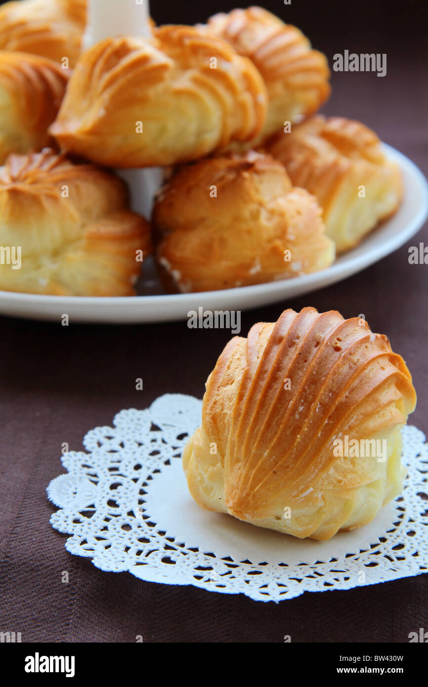 Cake profiteroles on a white plate on a brown background - Stock Image